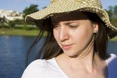 Portrait of beautiful woman. Thoughtful woman standing lakeside wearing a sun hat royalty free stock photo