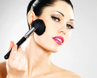 Beautiful woman applying blusher on face Royalty Free Stock Image