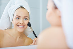 Portrait of beautiful woman applying eyeshadow Stock Photos