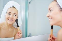 Portrait of beautiful woman applying eyeshadow Stock Images