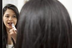Portrait of beautiful woman applying lipstick Royalty Free Stock Photo