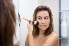 Portrait of beautiful woman applying makeup in bathroom Stock Photos