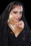 Portrait of a beautiful woman with arabian makeup in black paran. Ja isolated on dark background Royalty Free Stock Image