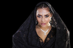 Portrait of a beautiful woman with arabian makeup in black paran. Ja isolated on dark background Stock Photography
