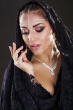 Portrait of a beautiful woman with arabian makeup in black paran Stock Images