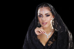 Portrait of a beautiful woman with arabian makeup in black paran. Ja isolated on dark background Stock Photo