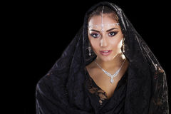 Portrait of a beautiful woman with arabian makeup in black paran. Ja isolated on dark background Stock Images