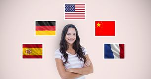 Portrait of beautiful woman with arms crossed standing by flags against beige background stock photography
