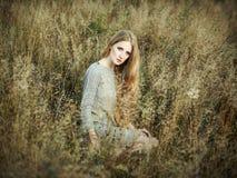Portrait of beautiful woman on autumn field Royalty Free Stock Image