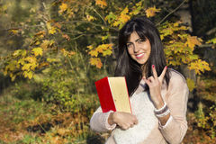 Portrait of a beautiful woman in the autumn park,holding a book. Portrait of a beautiful woman walking in the autumn park with a big book stock photo