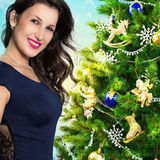 Portrait of a beautiful woman on the background of the Christmas tree. Stock Image