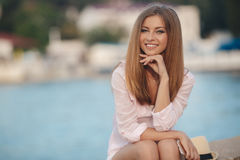 Portrait of beautiful woman on background of ocean. Portrait of a beautiful woman,brunette with long straight hair and gray eyes,a nice smile and beautiful white Royalty Free Stock Images