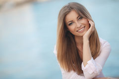Portrait of beautiful woman on background of ocean. Portrait of a beautiful woman,brunette with long straight hair and gray eyes,a nice smile and beautiful white Royalty Free Stock Image