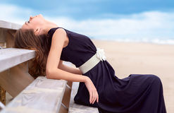 Portrait of a beautiful woman on the beach. She Looks at the sky. Young attractive woman near the ocean on a summer day stock photo