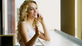 Portrait of beautiful woman with beaming smile talking on phone in cafe stock video
