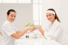 Portrait beautiful woman with beautician applying nail varnish to female clients nails Royalty Free Stock Photos