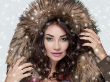Portrait of a beautiful woman with beautiful make-up and manicure in a fur coat royalty free stock photography