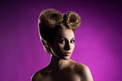 Portrait of a beautiful woman with a bizarre haircut. Over bright background Stock Image