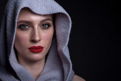 Portrait of a beautiful woman on a black background. With a knitted scarf on her head, beautiful make-up and with red lipstick Royalty Free Stock Images