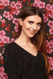 Portrait of a beautiful woman in a black dress. Background from a fabric in drawing flowers royalty free stock photo
