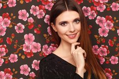Portrait of a beautiful woman in a black dress. Background from a fabric in drawing flowers stock photography
