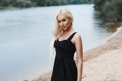 Portrait of a beautiful woman in a black dress on the beach at t. He river. outdoors Stock Image