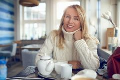 Portrait of a beautiful woman with blond long hair. And blue eyes looking at camera relaxed indoors Royalty Free Stock Photo