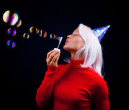 Portrait of a beautiful woman blowing bubbles. Attractive young woman blowing bubbles at party Royalty Free Stock Photo