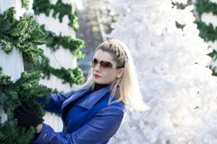 Portrait of the beautiful woman in a blue coat near a column Royalty Free Stock Image