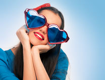 Portrait of a beautiful woman in blue with heart shaped glasses Stock Photos