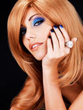 Portrait of a beautiful woman with blue nails, blue makeup. And  long red hairs  on black background Stock Image