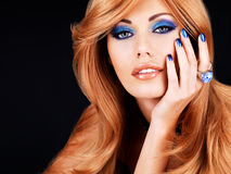 Portrait of a beautiful woman with blue nails, blue makeup. And  long red hairs  on black background Royalty Free Stock Images