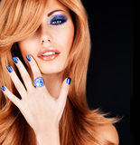 Portrait of a beautiful woman with blue nails, blue makeup. And  long red hairs  on black background Royalty Free Stock Photo