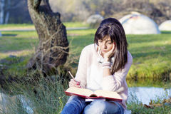 Portrait of a beautiful woman with book in the autumn park Stock Photography