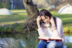 Portrait of a beautiful woman with book in the autumn park Royalty Free Stock Photo