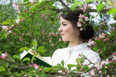 Portrait of beautiful woman with book in blooming summer garden Stock Photos