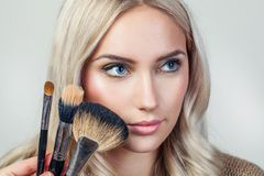 Portrait of beautiful woman with brush for make-up Stock Photos