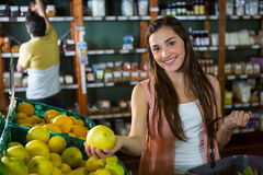 Portrait of beautiful woman buying sweet lime in organic section Stock Photos