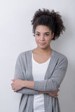 Portrait of a beautiful woman in a cardigan. Standing near white wall Stock Photos