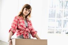 Portrait of beautiful woman carrying cardboard box Royalty Free Stock Image