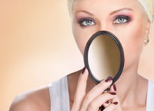 Portrait of beautiful woman closing face by small mirror Stock Photos