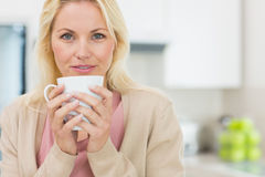 Portrait of a beautiful woman with coffee cup in kitchen Royalty Free Stock Photography
