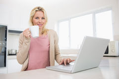 Portrait of beautiful woman with coffee cup using laptop in kitchen. Portrait of a beautiful young woman with coffee cup using laptop in the kitchen at home Stock Photography