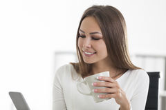 Portrait of beautiful woman with coffee in office Royalty Free Stock Photography