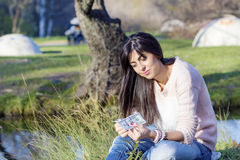 Portrait of beautiful woman counting money in the park Royalty Free Stock Images