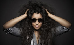 Portrait of beautiful woman with curly hairs and glasses Stock Images