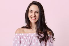 Portrait of beautiful woman with dark hair, smiles broadly, being in good mood, dressed in polka dot dress, poses against rosy stock photography