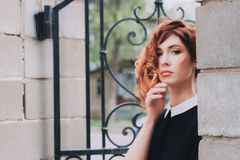 Portrait of a beautiful woman with dark red hair. With hair in grunge style, in a black blouse with white collar Stock Photography