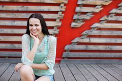 Portrait of a beautiful woman in denim shorts sitting on a wooden background. Royalty Free Stock Images