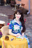 Portrait of beautiful woman in dress sitting in summer cafe Stock Photos